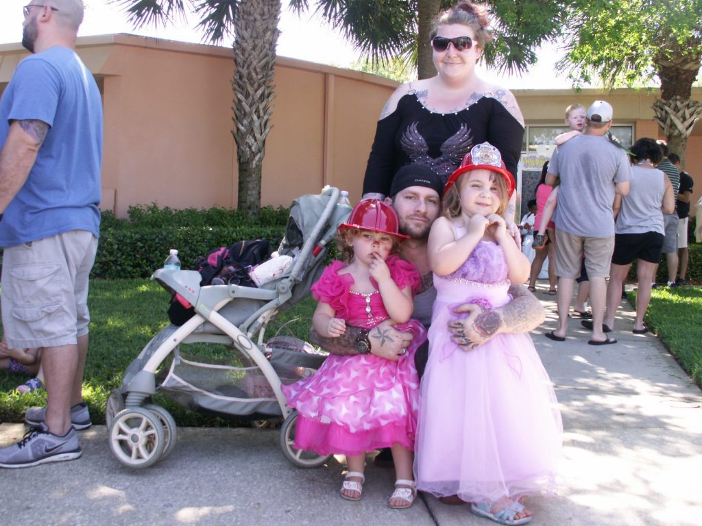 "Sisters Donelle, 3, left, and Skyla, 4, wearing their Easter gowns and fire hats, pose with their parents Michelle Peters and Donovan Molisee after having their picture taken with the Easter Bunny Saturday at Gulfport's Recreation Center. ""It's really nice,"" Michelle said of the event. ""We really appreciate it."""