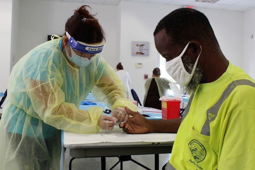 A man in a mask and yellow shirt gets a finger prick COVID-19 antibody test from a healthcare worker in protective gear
