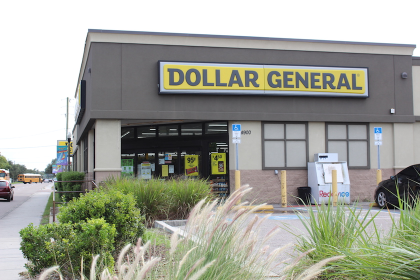 """A photo of the outside of Dollar General with a yellow sign that reads """"Dollar General."""""""
