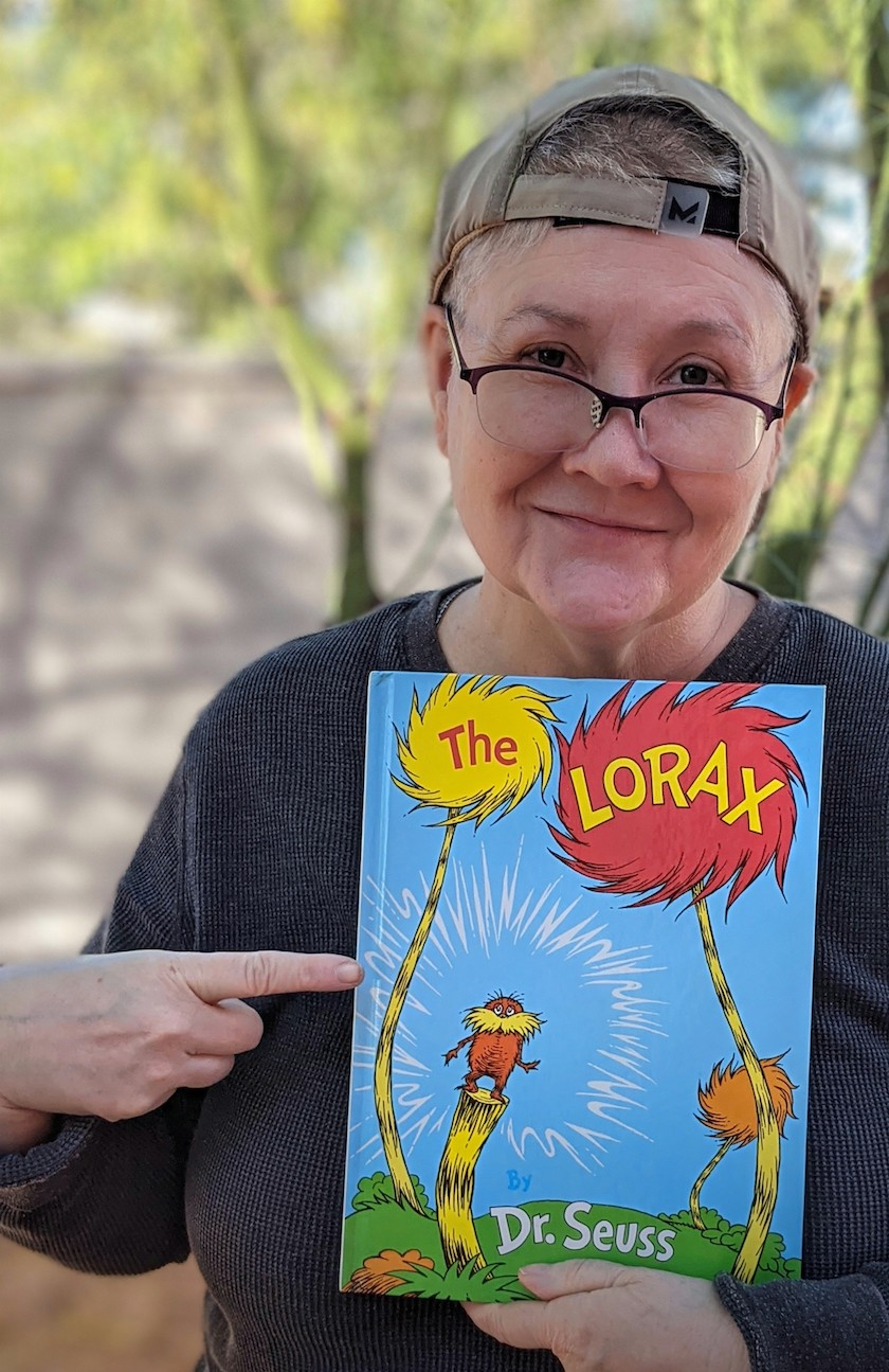 "A woman in glasses looking at the camera and holding a book ""The Lorax"" by Dr. Suess."
