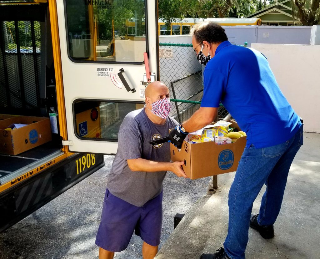 Left, Tim Delaney of Tampa Bay Network to End Hunger helps load boxes of food supplies with Joe Camera, a bus driver for Pinellas County Schools Photo by June Johns