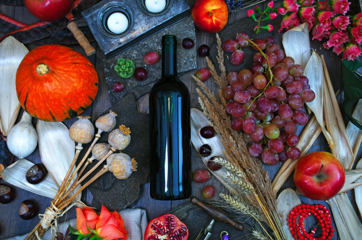 Wine bottle among spices and fruits on a grey cutting board/