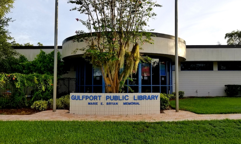 Exterior of the Gulfport Public Library with sign and flag poles
