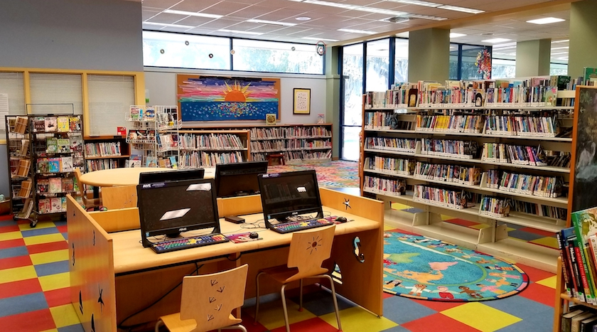 An interior photo of a library featuring book shelves and computers on a desk