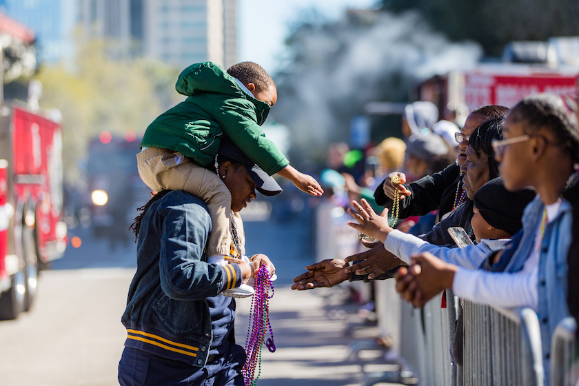 A man with a small boy on his shoulders passes out beads at a parade