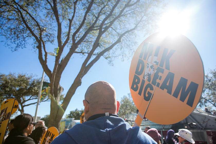"""The back of a man walking in the sun holding a sign that reads """"MLK Dream Big"""""""