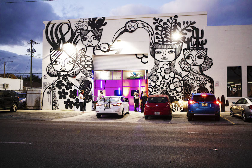 An outdoor scene of the front of a shop with a large black and white mural and cars parked in front.