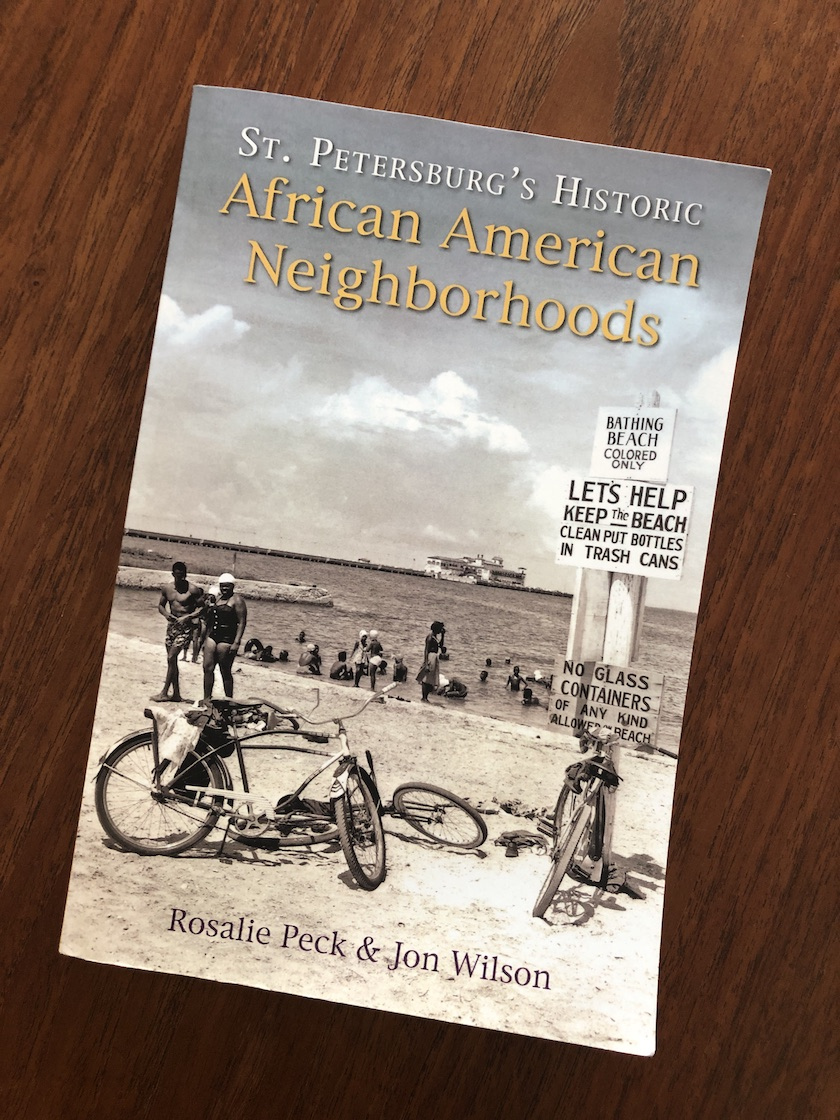 "The cover a book titled ""St. Petersburg's Historic African American Neighborhoods"" with a vintage photo of a beach scene."