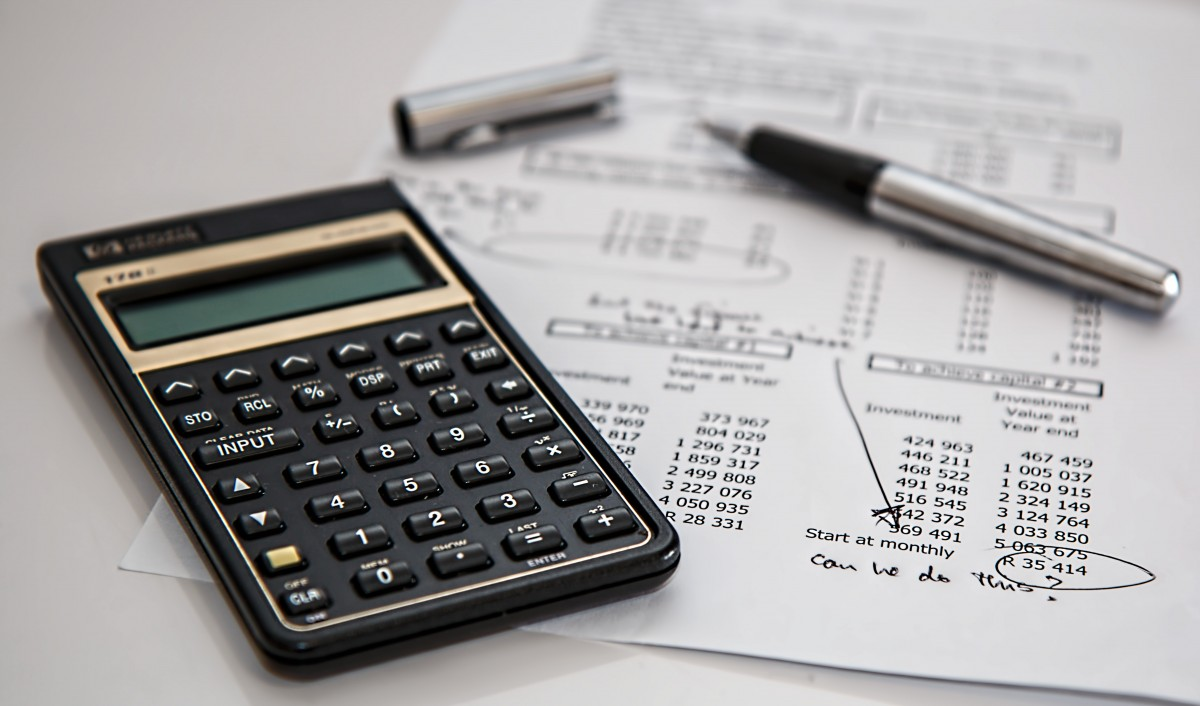 A calculator and pen laying askew partially done paper taxes