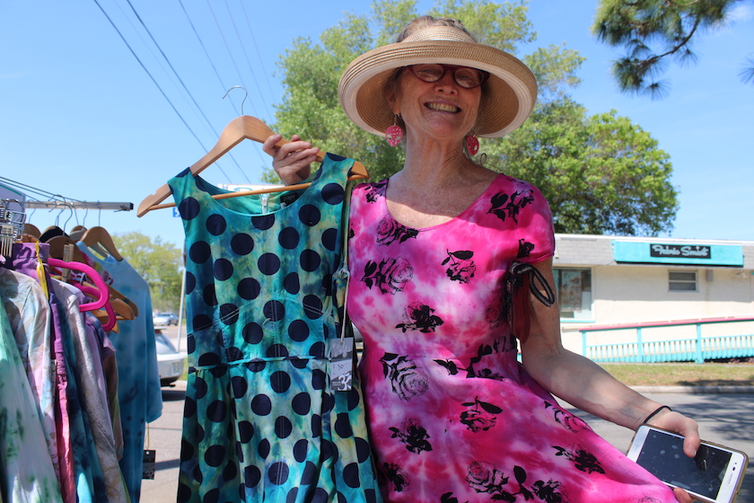 A woman in a hat and pink dress holds up a green polka-dot dress outside