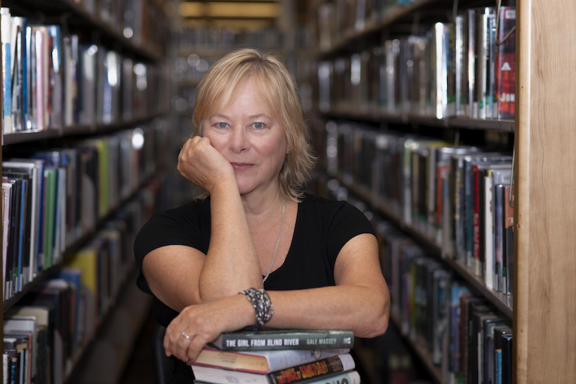 A woman standing in a library stacks leaning over a pile of books and looking into the camera.
