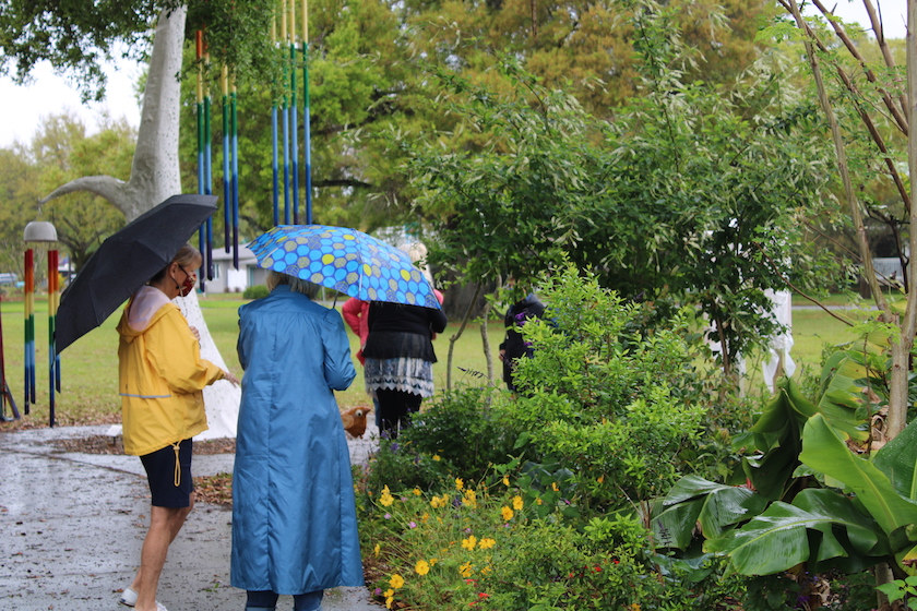 People holding umbrellas walking in a garden