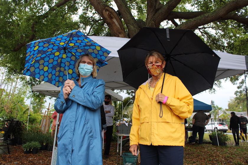 Two women with face masks, rain gear and umbrellas outside