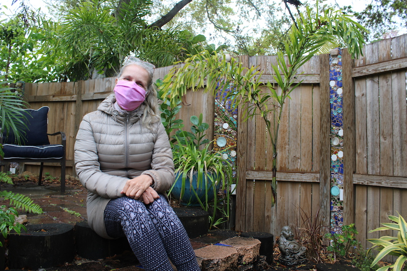 A woman in a pink face mask sitting in a garden