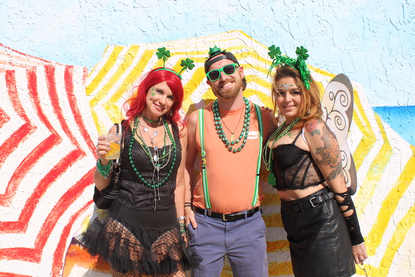 Three people pose in St. Patrick's Day costumes