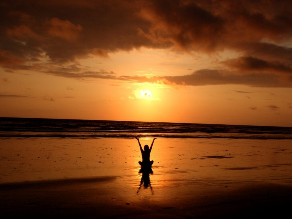 Person mediating on the beach during sunset