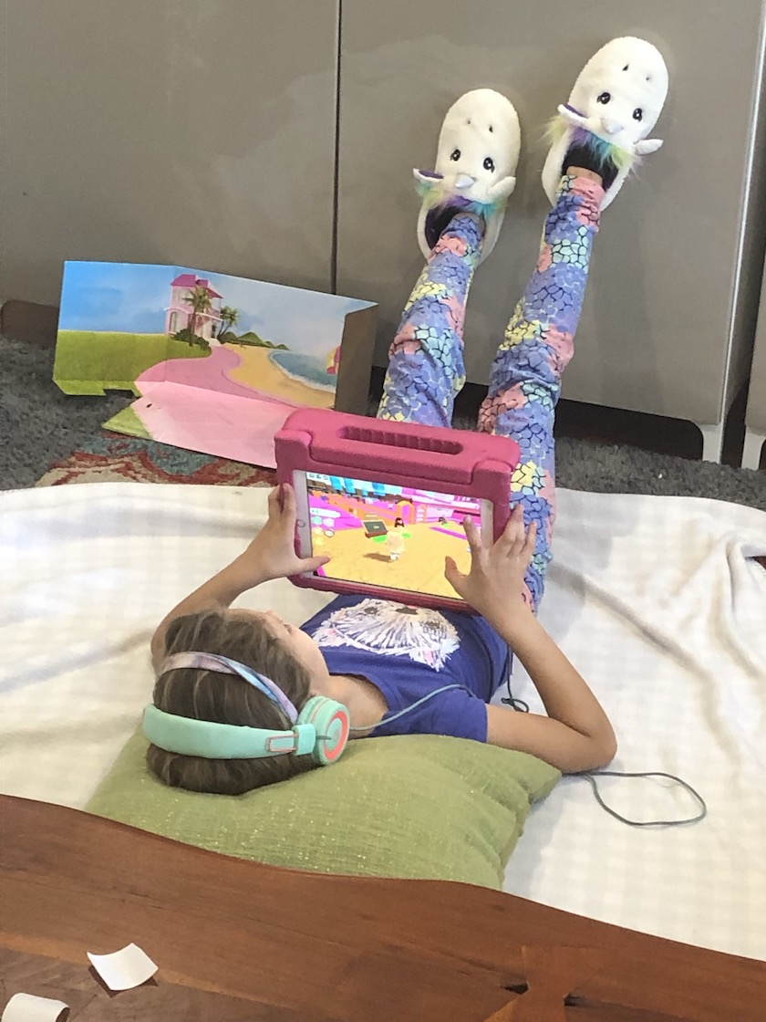 A girl laying on the ground playing with an iPad wearing headphones