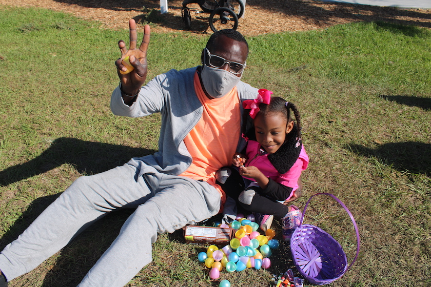A man in a face mask making a peach sign sitting in the grass with a young girl who has an Easter basket and a pile of eggs.