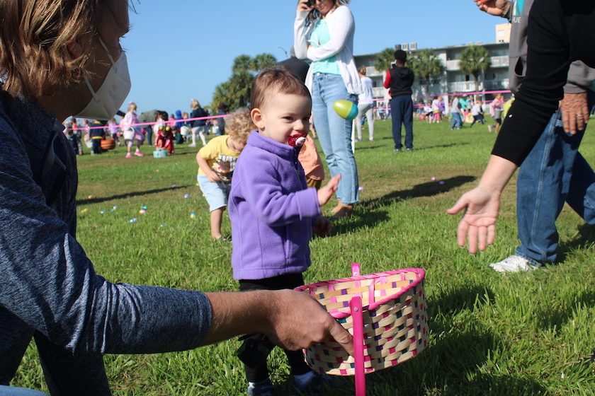 A small child with a pacifier in a field of people with an Easter basket