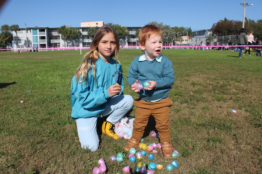 Two children in a field with a collection of Easter eggs