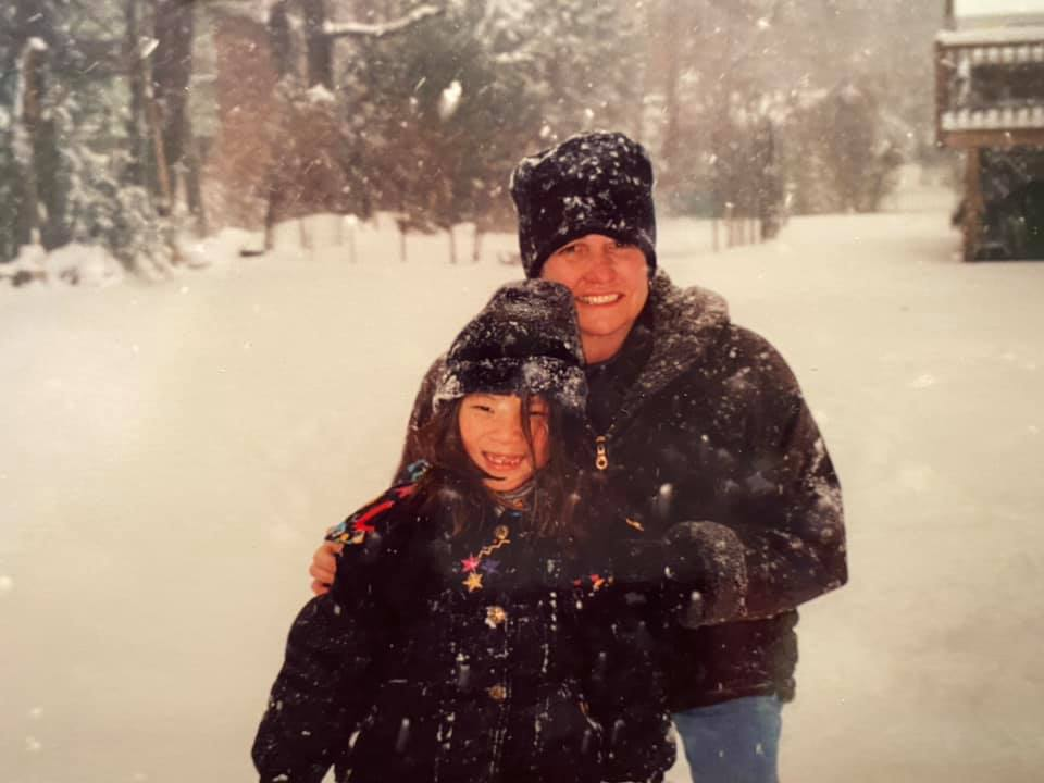 A woman and a girl bundled up in the snow