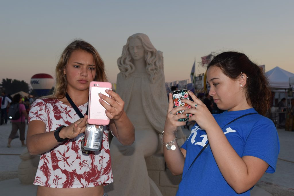 "Chloe Johnson, left, and Jessica Rogers, both of St. Petersburg, take selfies with a sand sculpture by artist Dmitry Klimenko of Moscow titled ""My Changing Woman"" as the sun prepares to set Saturday Nov. 19 in Treasure Island. The piece won second place in the eighth annual Sanding Ovations Masters Cup Sand Sculpture Competition and Music Festival held Nov. 16-20. First place went to a piece titled ""Biological Link"" by Jonathan Bouchard of Montreal, who also won first place in 2012, 2013 and 2014. ""We came here last year and the year before,"" Johnson said of the event, which also included craft and food vendors. ""It's like a family tradition."""