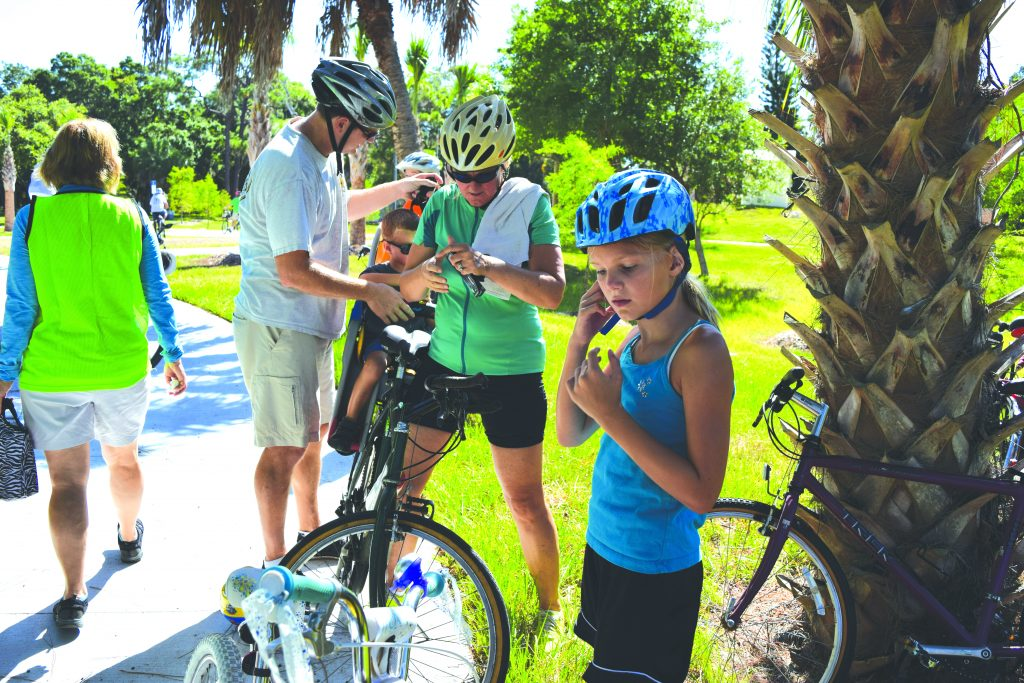 Sarah Weber, 9, of St. Petersburg, adjusts her helmet while her parents, Matthew and Mary, and her brother Henry, 4, get ready to head out again after a break at Clam Bayou Nature Preserve during Saturday's Skyway Marina District bike ride.