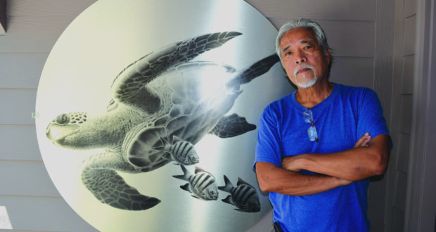 Artist Ray Domingo in front of a reproduction of one of his paintings on brushed aluminum hung at the entrance to his Gulfport home.