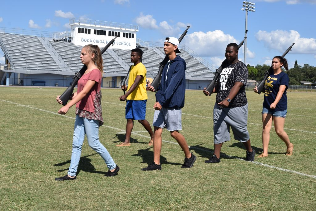 "Members of the Boca Ciega High School JROTC drill team practice with real but demilitarized weapons on Wednesday, October 19. ""A drill is a unique thing to do,"" says the drill team captain, Terry Morton, 17, in yellow shirt and blue shorts. ""Just to be so precise and have everybody look sharp."""