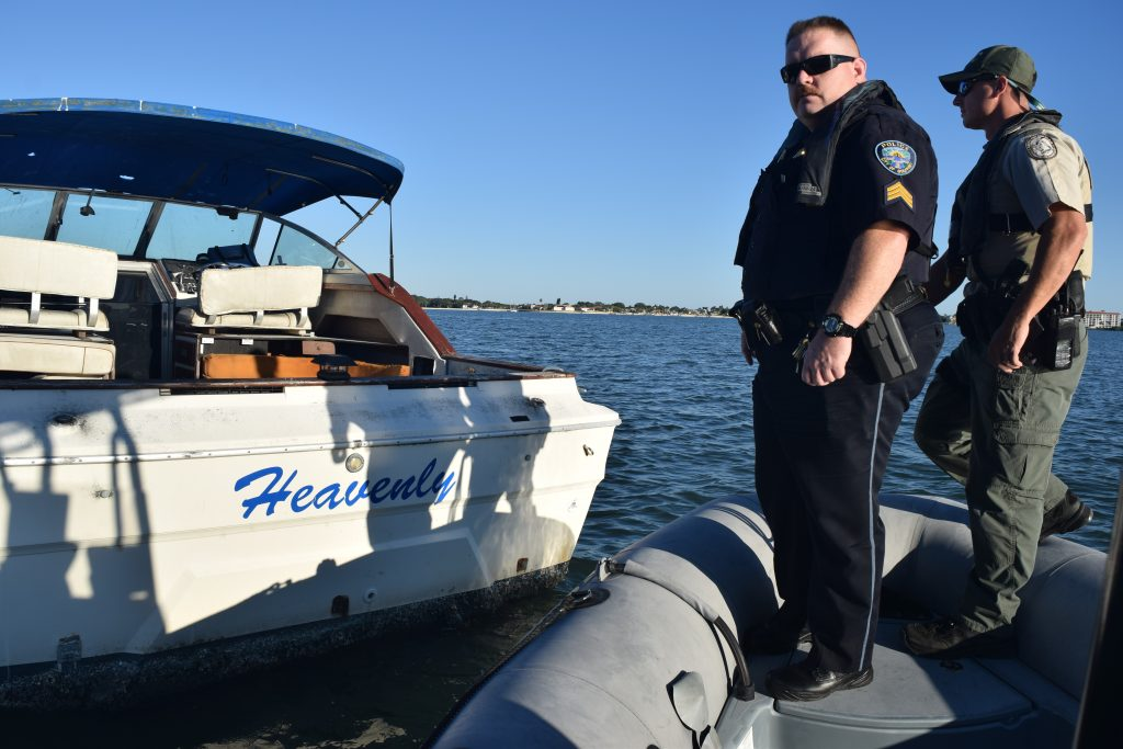 Sgt. Rob Burkhart, left, and Officer Randall Bibler of the Florida Fish and Wildlife Conservation Commission look over a vessel anchored in Boca Ciega Bay off Gulfport during the first coordinated marine patrol by the two agencies on Sunday, October 23.