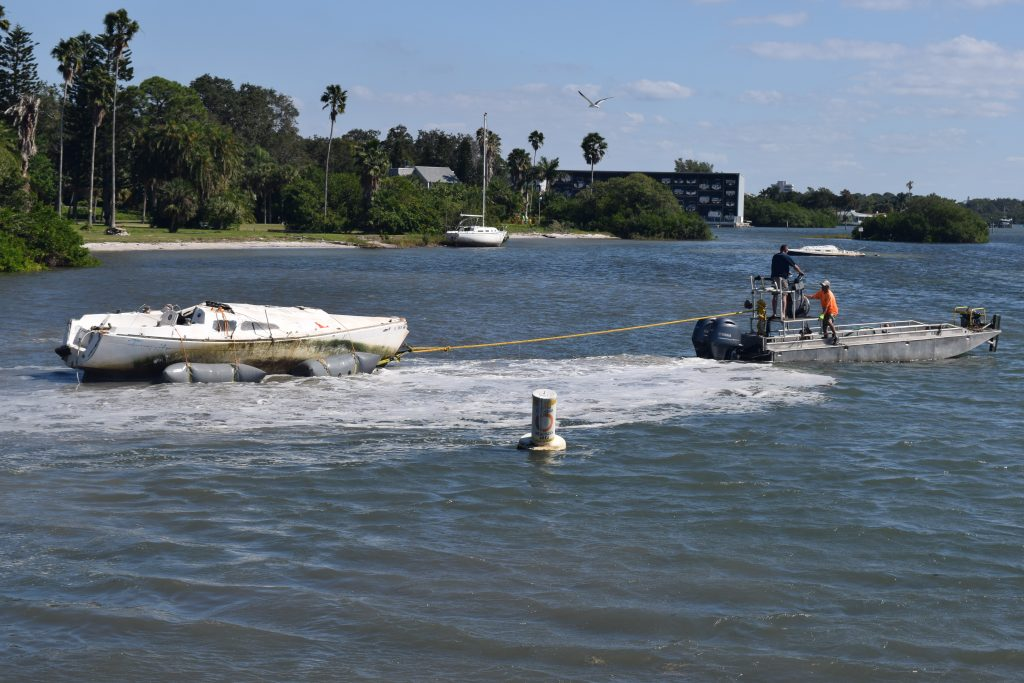 A Pinellas County contractor attempts to pull a derelict vessel grounded in front of Veteran's Park in Gulfport off the sand on Tuesday, November 1. Two other derelicts awaiting removal can be seen in the background.