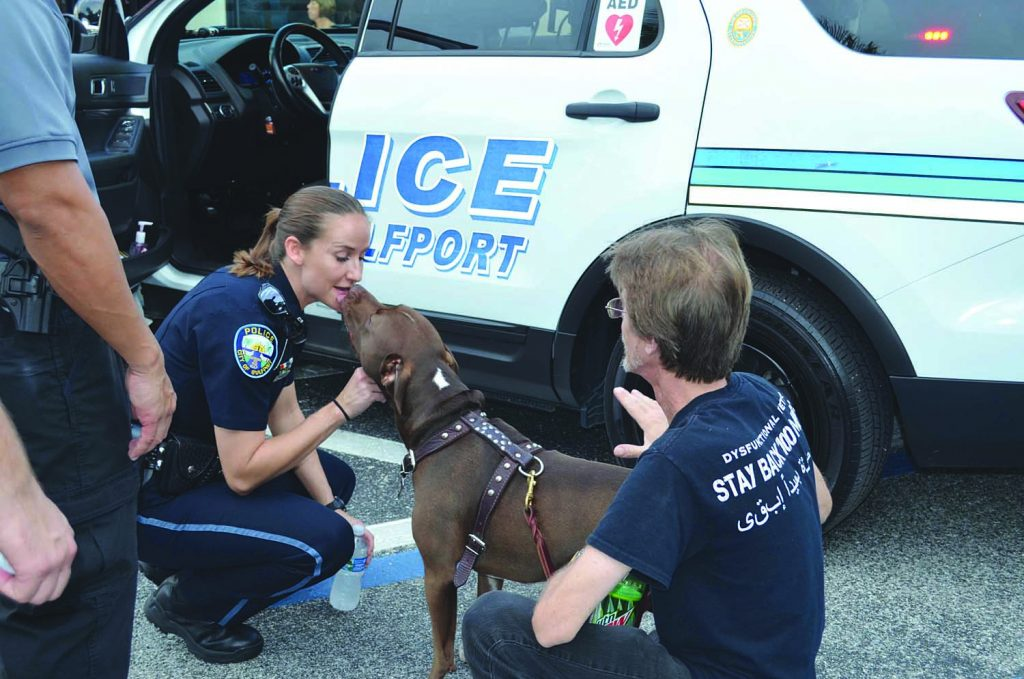 Gulfport Police Officer Eva Iwanowski, and the department's officer of the year in 2015, greets a four-legged attendee at Night Out.