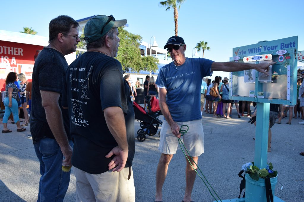 "David Westmark, co-founder of the Blue Turtle Green Bird Society environmental group with his wife Stephanie Cain, explains how the cigarette-butt ""voting"" kiosk works to visitors at the GeckoFest in Gulfport on Saturday, September 3."