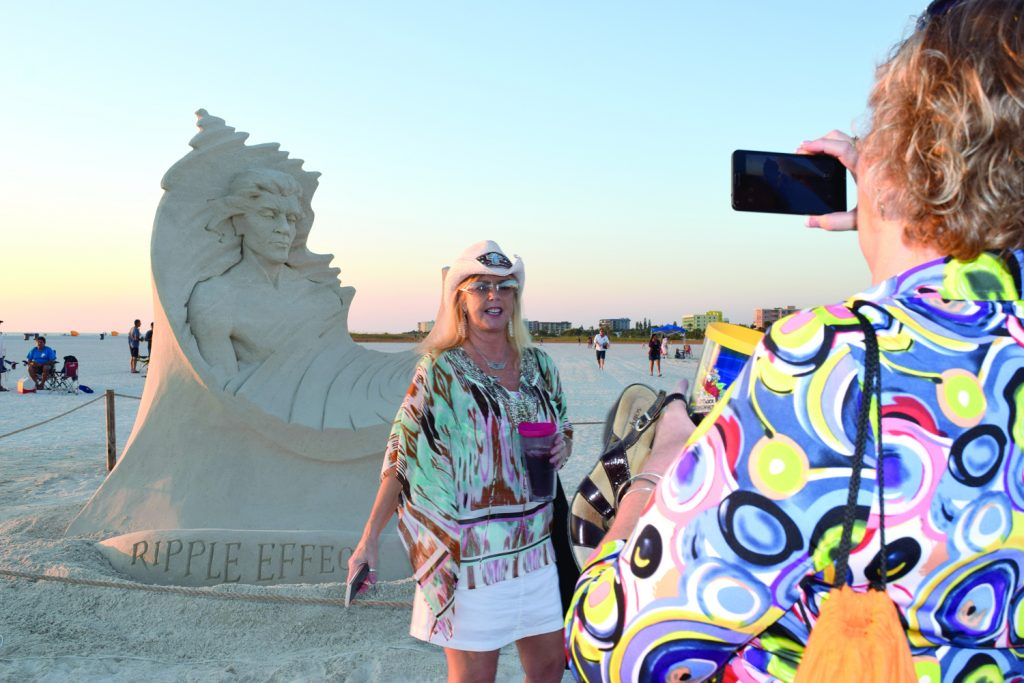 "Cindy Brown of Clearwater takes a photo of Ali Thompson, also of Clearwater, in front of a sand sculpture by artist Dan Belcher of St. Louis, titled ""Ripple Effect,"" as the sun prepares to set Saturday November 19 in Treasure Island. The sculpture was one of 10 competing in the eighth annual Sanding Ovations Masters Cup Sand Sculpture Competition and Music Festival held November 16 through 20. First place went to a piece titled ""Biological Link"" by Jonathan Bouchard of Montreal, who also won first place in 2012, 2013 and 2014. Brown said she's come to the contest every year since it started. Of the sculptures, she said, ""They're a little smaller this year, but very detailed."""