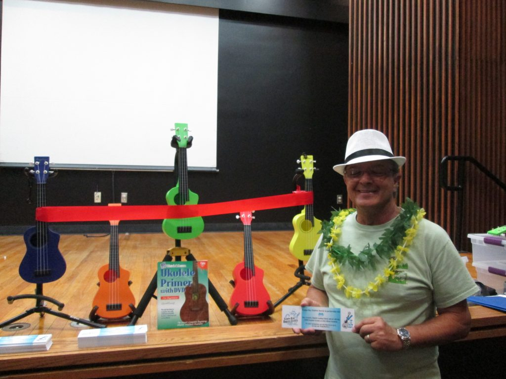 Cosmo Sagristano displays the ukuleles before the ribbon cutting.