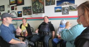 Gulfport Police Officer Zach Mills answers questions from community members at Coffee with a Cop.