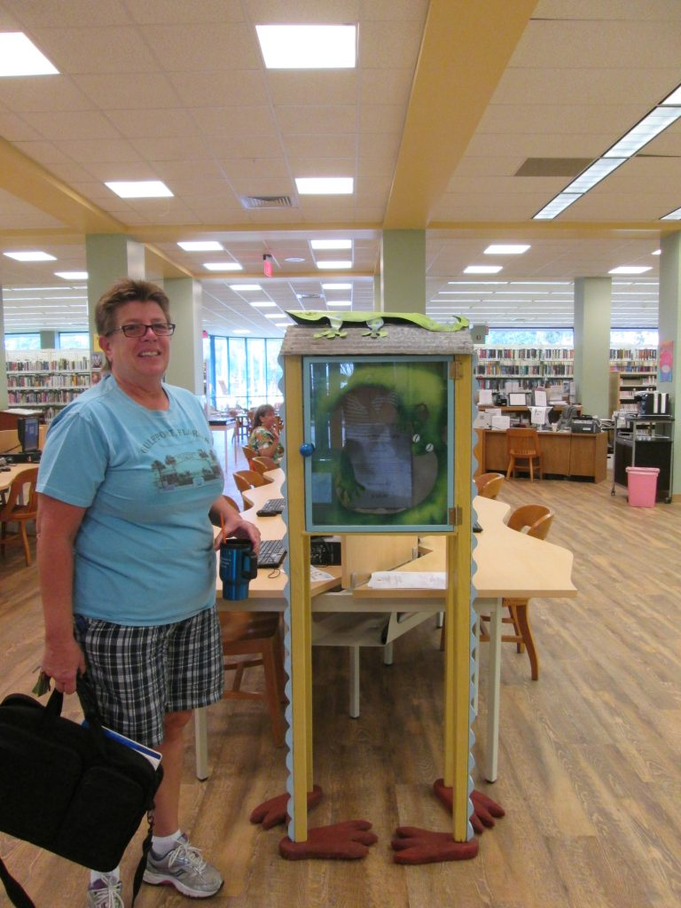 "Karen Gates admires ""Lizzie the Library"" by Gulfport artist Patsi Aguero on display at the Gulfport Public Library. Lizzie the Library is one of seven gecko art pieces created by seven local artists that will be auctioned at the live charity auction at Saturday's Gecko Ball."
