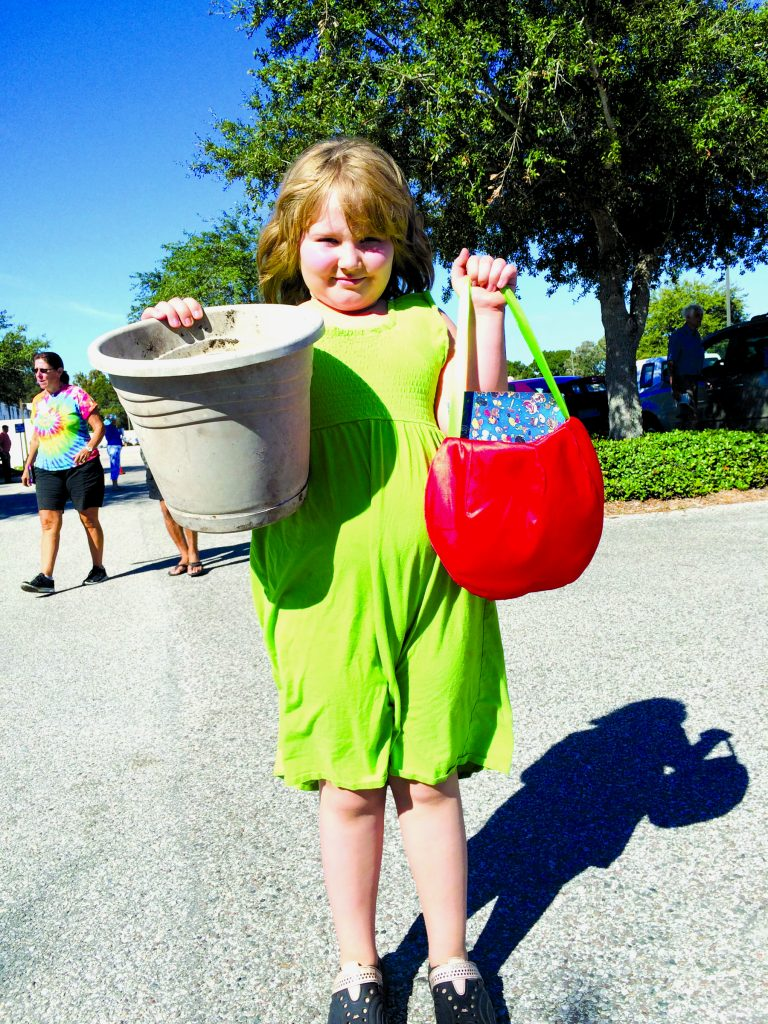 "Elizabeth McCaslin, 8, of Gulfport finds a book and a planter to upcycle from last Saturday's Junk in the Trunk event held last Saturday, October 24. ""I have basil seeds at home I am going to put in my new pot,"" she said."