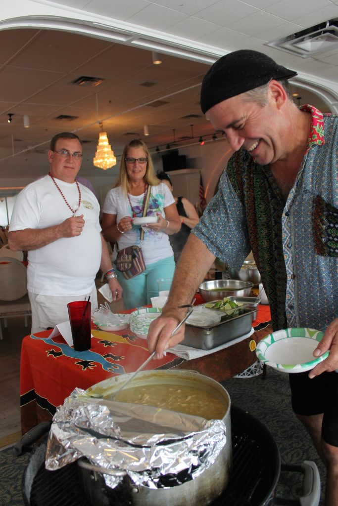 """Mark Amis of Little Tommie's Tiki in Gulfport serves up his turkey chili made with tomatillos and green chilis. """"The components of my chili are made separate and combined at the end,"""" he said at Sunday's event. """"This is how you taste all of the ingredients."""" Trish Carney and Ed Brown of Treasure Island, in background, seemed to love it."""