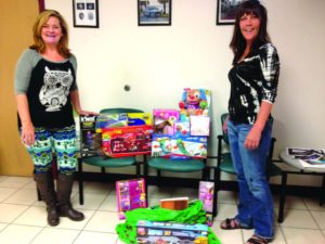 """Gulfport Merchants Association (GMA) volunteer Sherry Lynn (left) and Board Member Suzanne King present gifts for children collected for Operation Santa during GMA's """"Holiday Hoopla"""" event. Throughout 2014, the GMA was able to donate over $27,000 to charitable causes through proceeds from its events."""