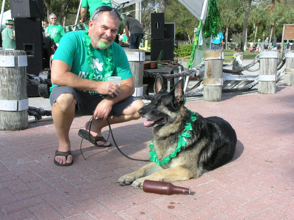 Al Deeter of Gulfport and his drinking buddy, Moke the German shepherd, pose during St. Patrick's Day festivities on Thursday, March 17 in Gulfport. Moke's bottle is actually a rubber squeaky toy.