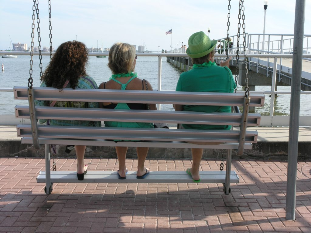 St. Patrick's Day, Gulfport style. While noisy celebrants mark St. Patrick's Day behind them on Shore Boulevard Thursday, March 17, three friends sit quietly on a swing, enjoying the view of Boca Ciega Bay and the fishing pier.