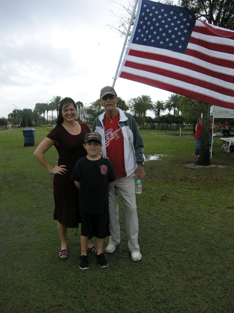 "Two veterans and a (future) firefighter: St. Pete Beach Mayor Maria Lowe, left, a veteran of the U.S. Army, poses with Korean War veteran George Stone of Seminole (Army Airborne) in front of an American flag after a rainstorm washed out a fundraising event sponsored by the Veterans of South Pinellas County in Horan Park in St. Pete Beach on Saturday, March 19. With them is Ian St. John of Lutz, 9, whose mother, Michelle St. John, is a lieutenant in the St. Pete Beach Fire Department. Asked whether he planned a military career in the future, Ian said: ""Kind of, but I'm mostly hoping to become a firefighter like my mom."""