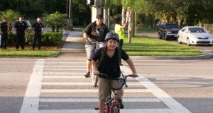 "Navarre Wigmore, 8, and his mother, Vickie Wehking, both of Gulfport, ride their bikes across Gulfport Boulevard at 52nd Street S. on their way to Gulfport Montessori Elementary School on the first day of classes. ""He was super excited,"" Wehking said of her son. ""We got his first grade teacher again … He was so happy."" Members of the Gulfport Fire Department, at rear left, were on hand to remind drivers to slow down now that school is back in session"