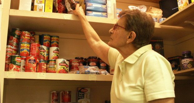 Volunteer Carol Gradl of Gulfport organizes items in the food pantry at the Gulfport Multipurpose Senior Center on Thursday, July 16.