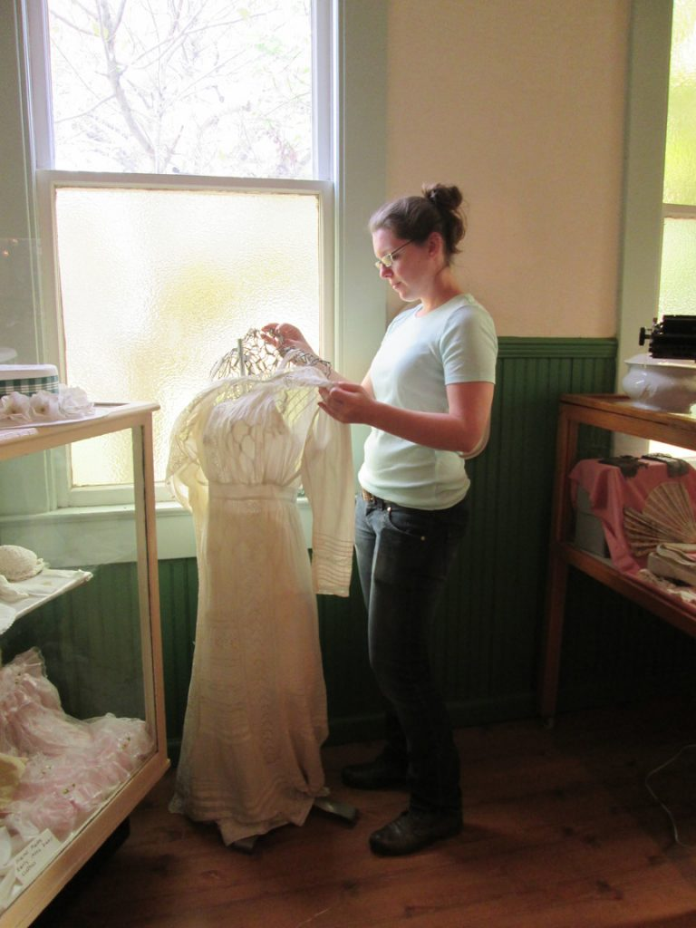 Cailey Klasson, a volunteer at the Gulfport Historical Museum, catalogues a vintage dress.