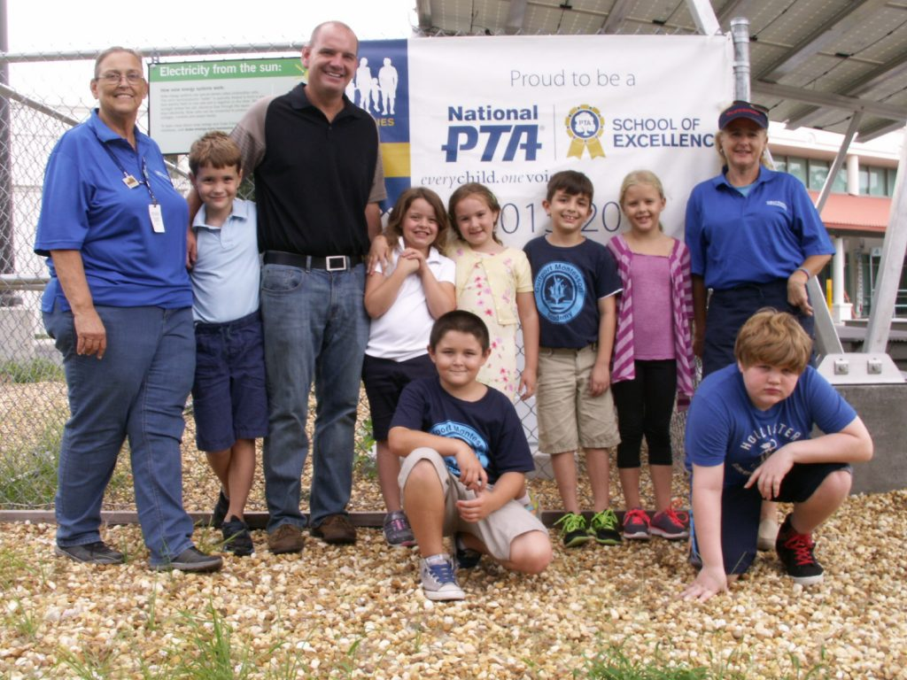 "Gulfport Montessori Elementary School students, volunteers and staff stand in front of a banner designating the school as a recipient of the ""National PTA School of Excellence"" award. The adults are, from left, PTA President Barbara Pace, Principal James Pribble and PTA Membership Chair Rhonda Muscat."