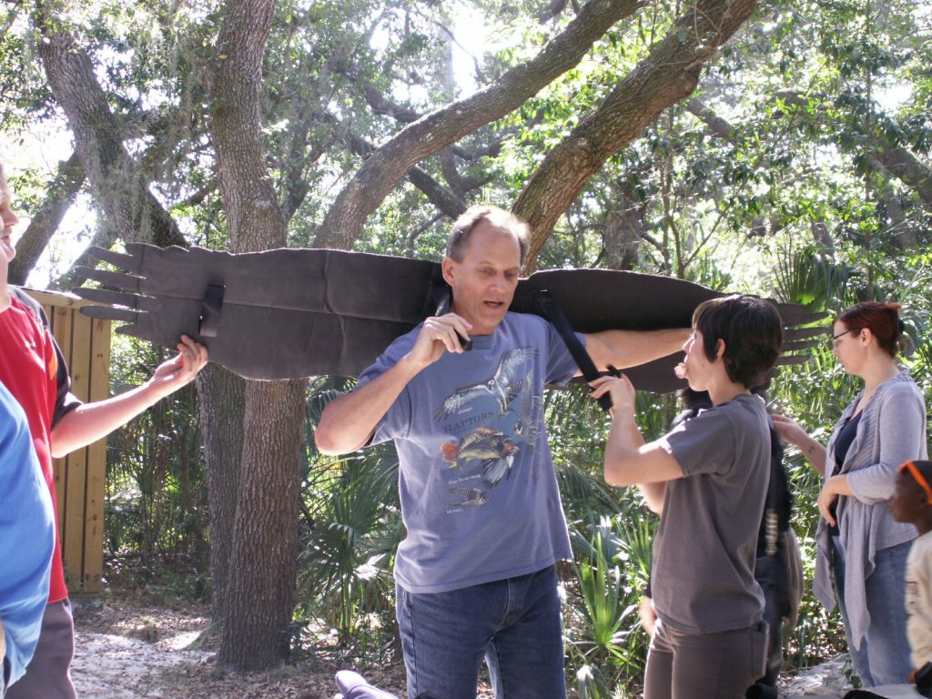 "Steve Tryon of Temple Terrace, tries on some eagle wings with the help of Boyd Hill volunteer Anastasia Steinbrunner of Clearwater. ""I love it,"" Tryon said of the festival. ""It's such an exciting opportunity to see our friends of the feather up close."""