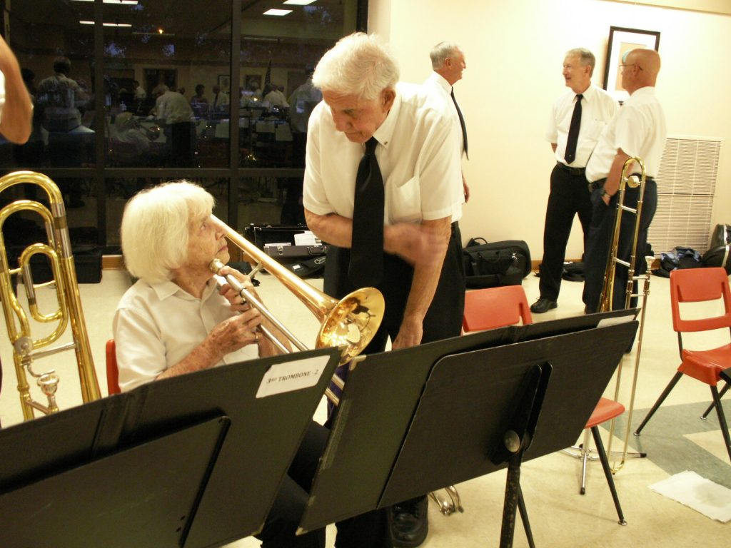 South Pasadena Community Band members Helen Cargo, trombone, and Seraphime Mike, assistant conductor, confer during the intermission of the band's April 15 performance at the Treasure Island Community Center.